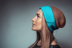 Profile portrait of a nice stylish woman isolated on gray background, wearing fashion knitted hat for youth, photo with copy space