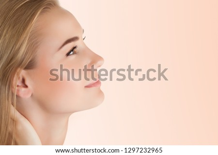 Profile portrait of a pretty woman with perfect skin isolated on clear background, using anti acne or anti aging cream, health and beauty care concept