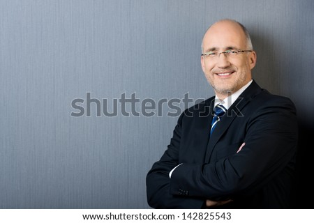 Profile portrait of a smiling and confident mature balding businessman, wearing a suit and a necktie, with arms crossed, in front of a gray wall with copy-space