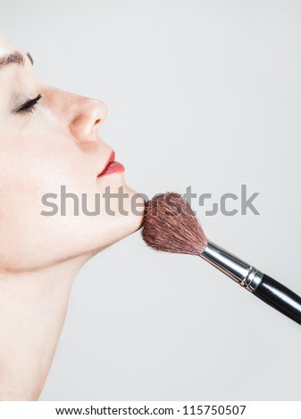 profile portrait of a womans face and a blush brush
