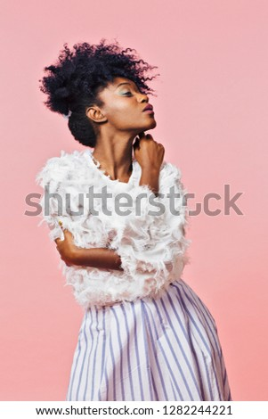 Profile portrait of a young woman with curly black hair and hands crossed, isolated on pink background	 #1282244221