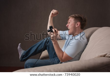 profile portrait of an excited young man playing video games on a gray background