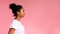Profile portrait of beautiful african teenage girl looking at copy space on pink studio background, panorama