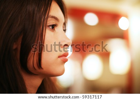 Profile portrait of beautiful young Asian woman indoors. Shallow DOF.