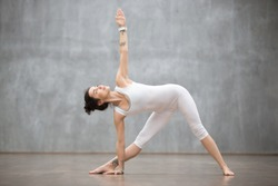 Profile portrait of beautiful young woman wearing white sportswear working out against grey wall, doing yoga or pilates exercise. Standing in Utthita Trikonasana, extended triangle pose. Full length