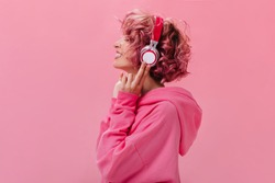 Profile portrait of charming pink-haired woman in massive headphones listening to music on isolated background. Curly girl in hoodie smiles.