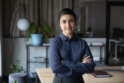 Profile portrait of confident young indian businesswoman standing in modern office with folded hands. Professional financial consultant lawyer ceo manager startup founder looking at camera.