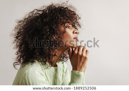 Profile portrait of curly brunette woman in green top looking straightforward. Dark-skinned lady poses on white background. Сток-фото ©