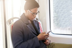Profile portrait of focused black hipster in trendy rectangular glasses browsing Internet, reading articles and posts on his social media page, using cell phone while riding home by subway train