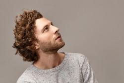 Profile portrait of gorgeous cute handsome young man with perfect features, bristle and reddish hair posing at blank copyspace wall in jumper, looking up with inspired dreamy facial expression