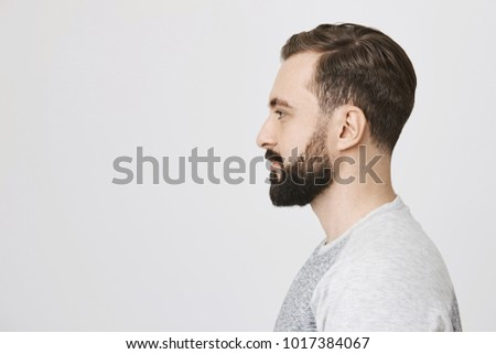 Profile portrait of handsome bearded adult european man with trendy haircut, standing over gray background. Hairdresser makes photo of new haircut he did for visitor to post it on site