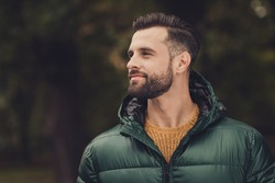 Profile portrait of handsome person look interested far away wearing warm clothing walking outdoors