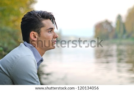 Profile portrait of handsome young male model on river banks