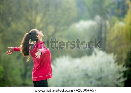 Profile portrait of happy sporty woman relaxing in park. Joyful female model breathing fresh air outdoors. Healthy active lifestyle concept. Copy space