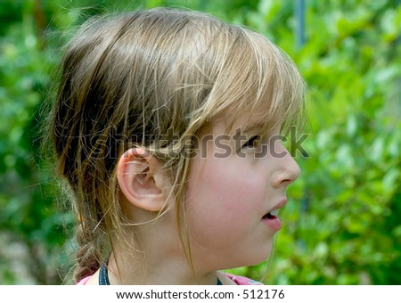 Profile portrait of little girl close-up at sunny day
