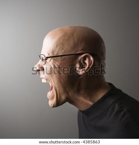 Profile portrait of mid-adult Caucasian male screaming.