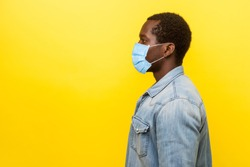 Profile portrait of serious young man with surgical medical mask looking left side with calm confident expression, blank copy space for text. indoor studio shot isolated on yellow background