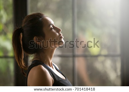 Profile portrait of young attractive yogi woman breathing fresh air, her eyes closed, meditation pose, relaxation exercise, working out wearing black sportswear top, close up image, window background