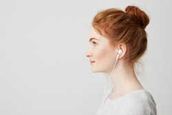 Profile portrait of young beautiful tender redhead girl with bun in headphones smiling over white background.