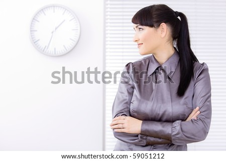 Profile portrait of young businesswoman standing with arms crossed on office, looking feft.