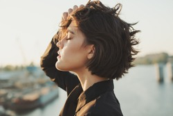 Profile portrait of young stylish woman.  Urban landscape port on background. Sunset city port and sky