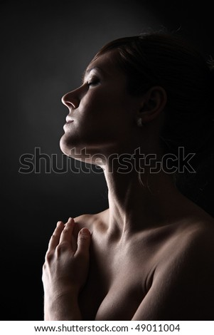 Profile portrait of young woman in studio on black background