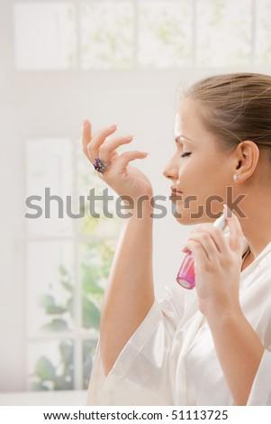 Profile portrait of young woman wearing white silk bathrobe applying perfume.