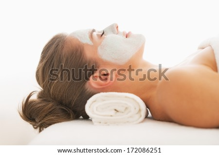 Profile portrait of young woman with revitalising mask on face laying on massage table
