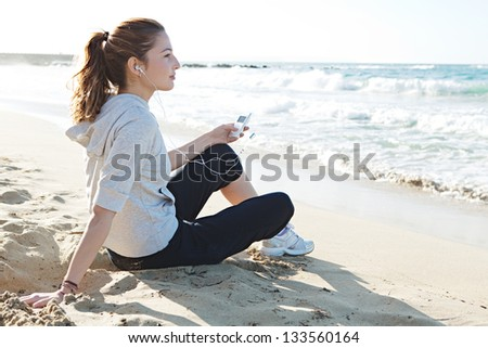 Profile portrait view of a young woman sitting on a fine sand beach shore, holding a music player and listening to music with her head phones being thoughtful.