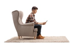Profile shot of a guy sitting in an armchair and typing on a mobile phone isolated on white background