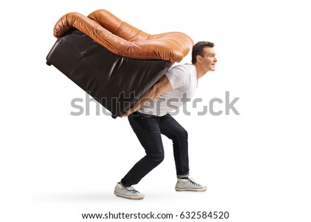 Profile shot of a young guy carrying an armchair on his back isolated on white background