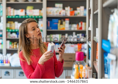 Profile shot of beautiful young woman shopping at pharmacy. Woman holding medication container while talking on cell phone.  Woman holding medication box and dialing on cell phone