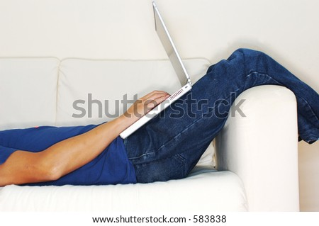 Profile shot of casual guy lying down working on laptop (high key)