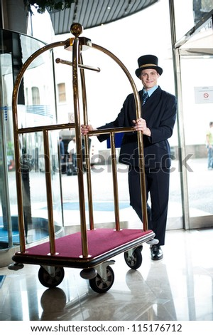 Profile shot of doorman holding cart at the entrance of hotel