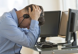 Profile shot of male exhausted trader with head in hands leaning at computer desk in office