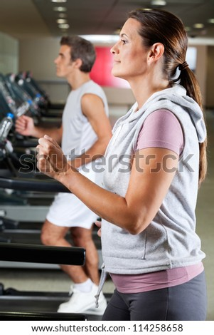 Profile shot of mature woman and man running on treadmill in health club