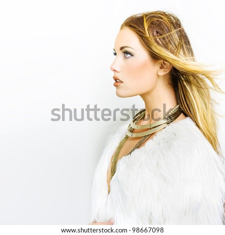 Profile shot of woman wearing big gold necklaces and white feather top looking to copyspace in a hair makeup and fashion concept