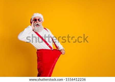 Profile side photo of crazy funky white beard hair santa claus in hat hold big size pants lose weight x-mas celebrate noel diet effect scream isolated yellow color background #1556412236