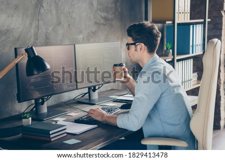 Profile side photo of focused guy administrator have many testing computer work look screen sit desk hold take-out mug coffee beverage in workplace workstation