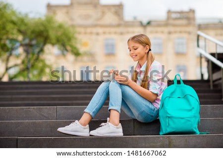 Profile side photo of lovely kid with pigtails ponytails writing wearing checkered plaid t-shirt denim jeans sitting near college