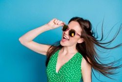 Profile side photo of pretty candid woman touch glasses enjoy rejoice weekend air wind blow hairstyle wear good look clothes isolated over blue color background