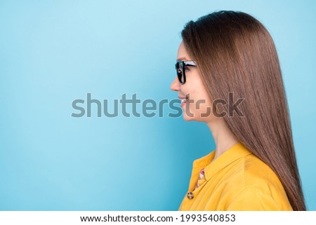 Profile side photo of young cheerful girl happy positive smile look empty space confident isolated over blue color background