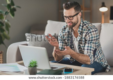 Profile side photo of young man happy positive smile sit couch home speak talk videocall laptop meeting remote work seminar Stockfoto ©