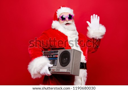 Profile side view aged funky white winter beard mature Santa modern star spectacles headwear costume hold audio record player make gesture hello goodbye isolated on December noel red background #1190680030