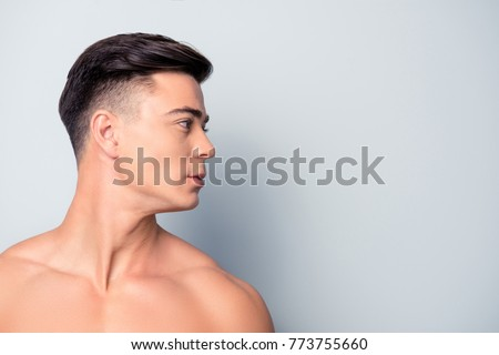 Profile side view half-faced close up portrait of confident handsome shaven with flawless skin man without shirt, isolated on grey background, copyspace