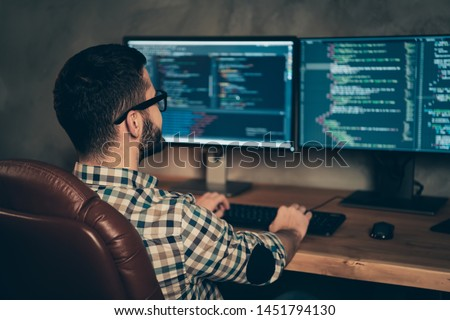 Profile side view of brunet bearded guy ceo boss chief executive designer professional expert specialist sitting in front of screen creating web site at wooden industrial interior work place station