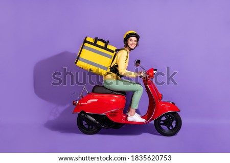 Profile side view of her she nice attractive cheerful girl riding bike delivering, bringing cafe food order fast speed express isolated bright vivid shine vibrant lilac violet purple color background Stockfoto ©