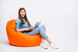 Profile side view of her she nice attractive lovely cute positive cheerful cheery girl sitting in bag chair using laptop working remotely isolated over light white color background