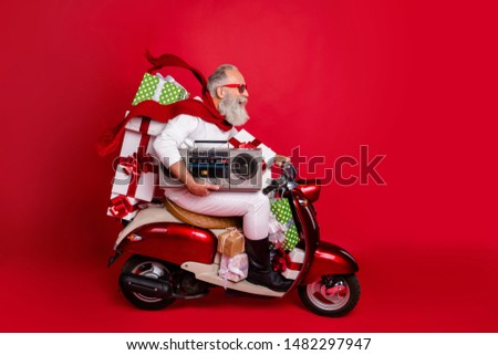 Profile side view of his he nice attractive cheerful cheery funky bearded gray-haired man carrying cool desirable purchase things eve noel celebration isolated on bright vivid shine red background #1482297947