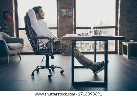 Profile side view of his he nice attractive chic elegant confident cheerful man qualified expert shark sitting in chair having rest at modern loft brick industrial style interior workplace station